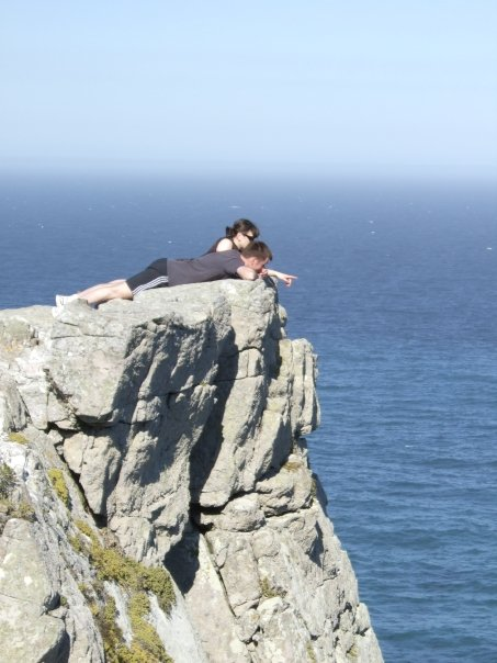 Two people lying down on the edge of a cliff