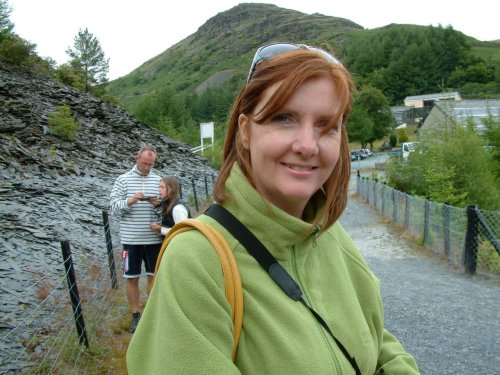 Picture of a lovely red-haired lady smiling in front of some hills