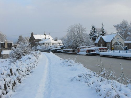 Frozen canal with snowy towpath and boats