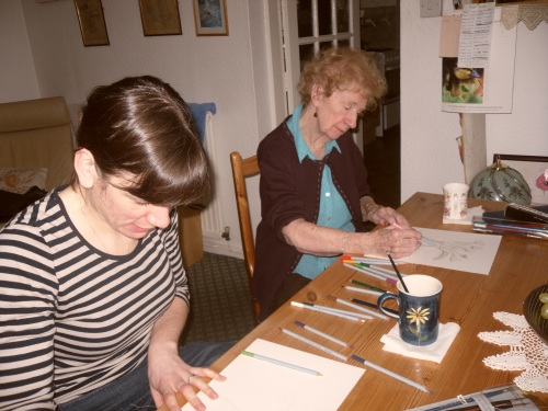 A grandmotrher and her grown-up grand-daughter, painting together at a table
