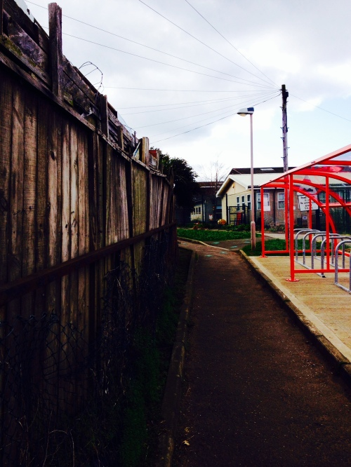 photo of path past rickety fences and red bike shelter