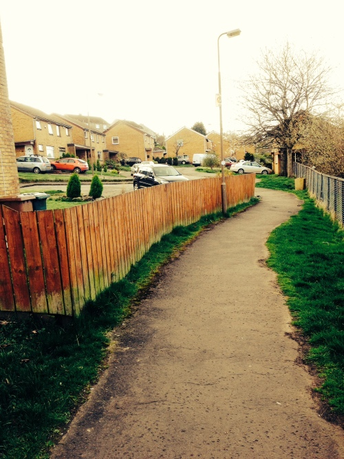 path leading past fence and towards brick houses